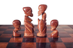 Family with husband, wife and two children, represented by four pieces of wooden chess king, queen and two pawns Royalty Free Stock Images