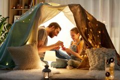 Family playing tea party in kids tent at home. Family, hygge and people concept - happy father and little daughter playing tea party in kids tent at night at stock photos