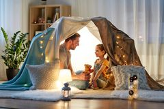 Happy family playing with toy in kids tent at home. Family, hygge and people concept - happy father with teddy bear toy and little daughter playing in kids tent royalty free stock image