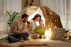 Happy family reading book in kids tent at home. Family, hygge and people concept - happy mother, father and little daughter reading book with torch light in kids royalty free stock photography