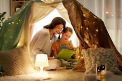 Happy family reading book in kids tent at home. Family, hygge and people concept - happy mother and little daughter reading book in kids tent at night at home royalty free stock images
