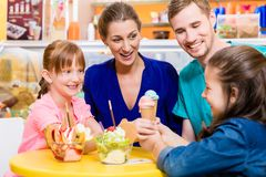 Family in ice cream parlor. Enjoying a sweet dessert stock images