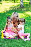 Family with ice cream. Young beautiful women with girls kids daughters sitting on grass, smiling eating ice cream Stock Photo