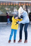 Family ice skating. Happy mother and her little son having fun ice skating together at winter Stock Photo
