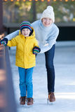 Family ice skating. Happy family of mother and her son enjoying ice skating together at winter at outdoor skating rink Stock Photos