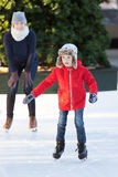 Family ice skating. Little boy learning ice skating and his mother watching and cheering up at outdoor skating rink, having winter vacation fun Royalty Free Stock Photo