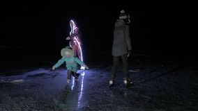 Family is ice skating night. Girls and boys to ride figure ice skates in nature. Mother, daughter and son riding. Family is ice skating night. Girls and boys to stock video footage