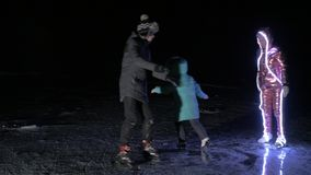 Family is ice skating night. Girls and boys to ride figure ice skates in nature. Mother, daughter and son riding. Family is ice skating night. Girls and boys to stock footage