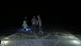 Family is ice skating night, make selfie. Mother, father, daughter and son riding together on ice in cracks. Outdoor. Winter fun for athlete nice winter weather stock footage