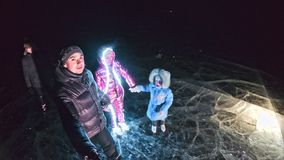Family is ice skating night, make selfie. Mother, father, daughter and son riding together on ice in cracks. Outdoor. Winter fun for athlete nice winter weather stock video