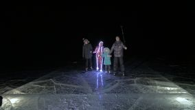 Family is ice skating night, make selfie. Mother, father, daughter and son riding together on ice in cracks. Outdoor. Winter fun for athlete nice winter weather stock video footage