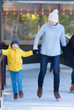Family ice skating. Young mother and her son ice skating together at outdoor skating rink at winter Stock Photography