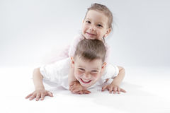 Family Ideas and Concepts. Portrait of Happy and Smiling Brother and Sister Playing Together Underneath. Posing Against White. Horizontal Image Stock Photography