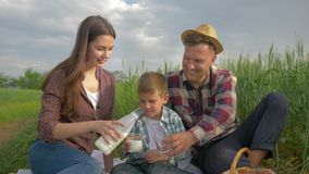 Family idyll, happy woman pours milk into glasses to child boy and smiling man in hat while relaxing on picnic outdoors