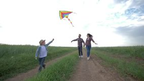 Family idyll, little boy with kite in his hands runs on countryside in slow motion on background of young parents and