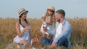 Family idyll, young happy couple with little nice child girl drink milk at weekend countyside picnic in sunny crop. Season of yellow grain meadow against blue stock footage