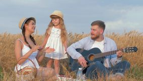 Family idyllic picnic, merry young couple with cute little daughter play musical string instrument and have fun in. Harvest wheat field shining by warm autumn stock video footage