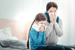 Ill exhausted natives sneezing and closing their eyes. Family illness. Ill exhausted sad natives being in the bedroom sneezing and closing their eyes Royalty Free Stock Photos