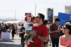 A family, including a baby kid with ear sound protectors, walk at Heineken Primavera Sound 2013 Festival Royalty Free Stock Photo