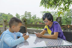 Family indulge in smartphone. Chinese mom and son using smartphone face to face outdoor royalty free stock images