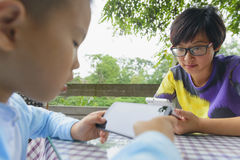 Family indulge in smartphone. Chinese mom and son using smartphone face to face outdoor royalty free stock image
