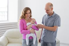 Family, infant and children concept - Happy mother and father with their baby stock image