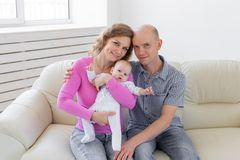 Family, infant and children concept - Happy mother and father with their baby stock photos