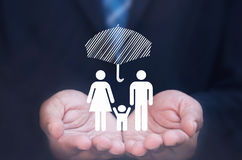 Family insurance. Business man holding a family icon protected by an umbrella Stock Photography
