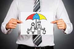 Family insurance concept. Businessman holding paper with drawing of a family under the umbrella stock image