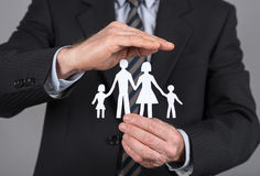 Family insurance concept. Insurance concept, man protecting a family with his hand stock photography