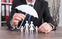 Family insurance concept. Family protected with an umbrella by an insurer - insurance concept stock photos