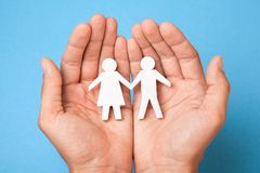 Family insurance. Man holds couple of men and women in their hands. Care Stock Images