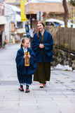 Family in Japan. Family of mother and daughter wearing yukata traditional Japanese kimono at street of onsen resort town in Japan. Translation of text on wooden Royalty Free Stock Photos