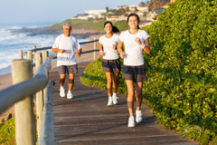 Family jogging beach. Active family jogging by the beach in the morning royalty free stock photo