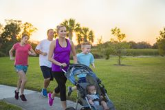 Family jogging and exercising outdoors together. Beautiful, fit young family walking and jogging together outdoors along a paved sidewalk in a park pushing a stock photos