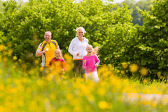 Family jogging in the meadow for fitness. Happy Family with two girls running or jogging for sport and better fitness in a meadow in summer stock photography