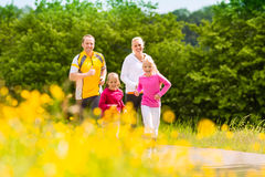 Family jogging in the meadow for fitness. Happy Family with two girls running or jogging for sport and better fitness in a meadow in summer Stock Photo