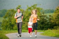 Family jogging outdoors Stock Photo