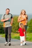 Family jogging outdoors. Family doing sport by jogging outdoors with the kids in a beautiful summer landscape in the late afternoon sun Stock Photos