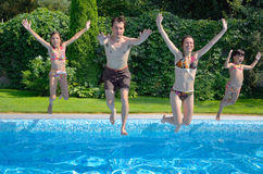 Family jump to swimming pool. Happy family with kids jumping to swimming pool, smiling parents and children having fun on summer vacation Stock Images