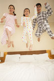Family Jumping on Bed Together Royalty Free Stock Image