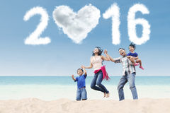Family jumping at coast with numbers 2016. Portrait of cheerful family jumping on the coast on the beach with cloud shaped numbers 2016 Royalty Free Stock Images
