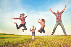 Family jumping  in the field Royalty Free Stock Image