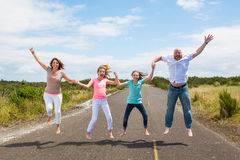 Family jumping together on the road Royalty Free Stock Photo