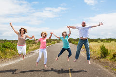 Family jumping together on the road Royalty Free Stock Image