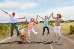 Family jumping together on the road Royalty Free Stock Photos