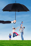 Family jumping under umbrella on the meadow. Portrait of happy family jumping on the meadow under umbrella. Life and family insurance concept Stock Photos
