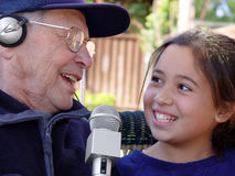 Family karaoke. Grandfather and granddaughter singing together Royalty Free Stock Images