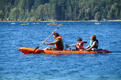 Family kayak in a lake. People, family, men women and children kayaking in the lake deep blue water. Enjoing vacaciones, weekend, active sports. Sunny day, clear royalty free stock image