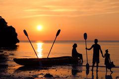 Family kayaking on the beach with sunset background. Stock Images